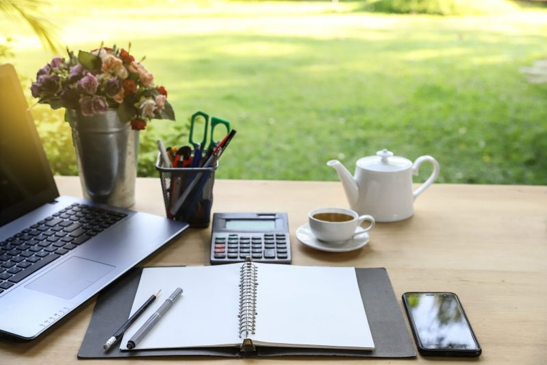 Garden office table with note book ,pen, smartphone,computer business, calculator and cup of tea on green garden background