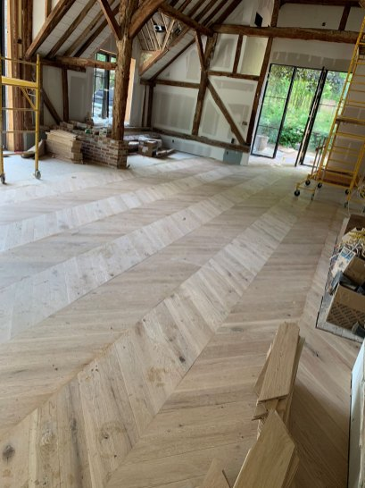 select white oak chevron floor installation in Watermill