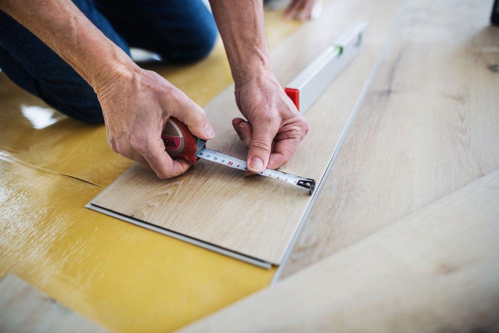 man installing vinyl plank flooring