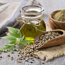 Hemp seed oil next to a scoop filled with hemp seeds | Ingredients