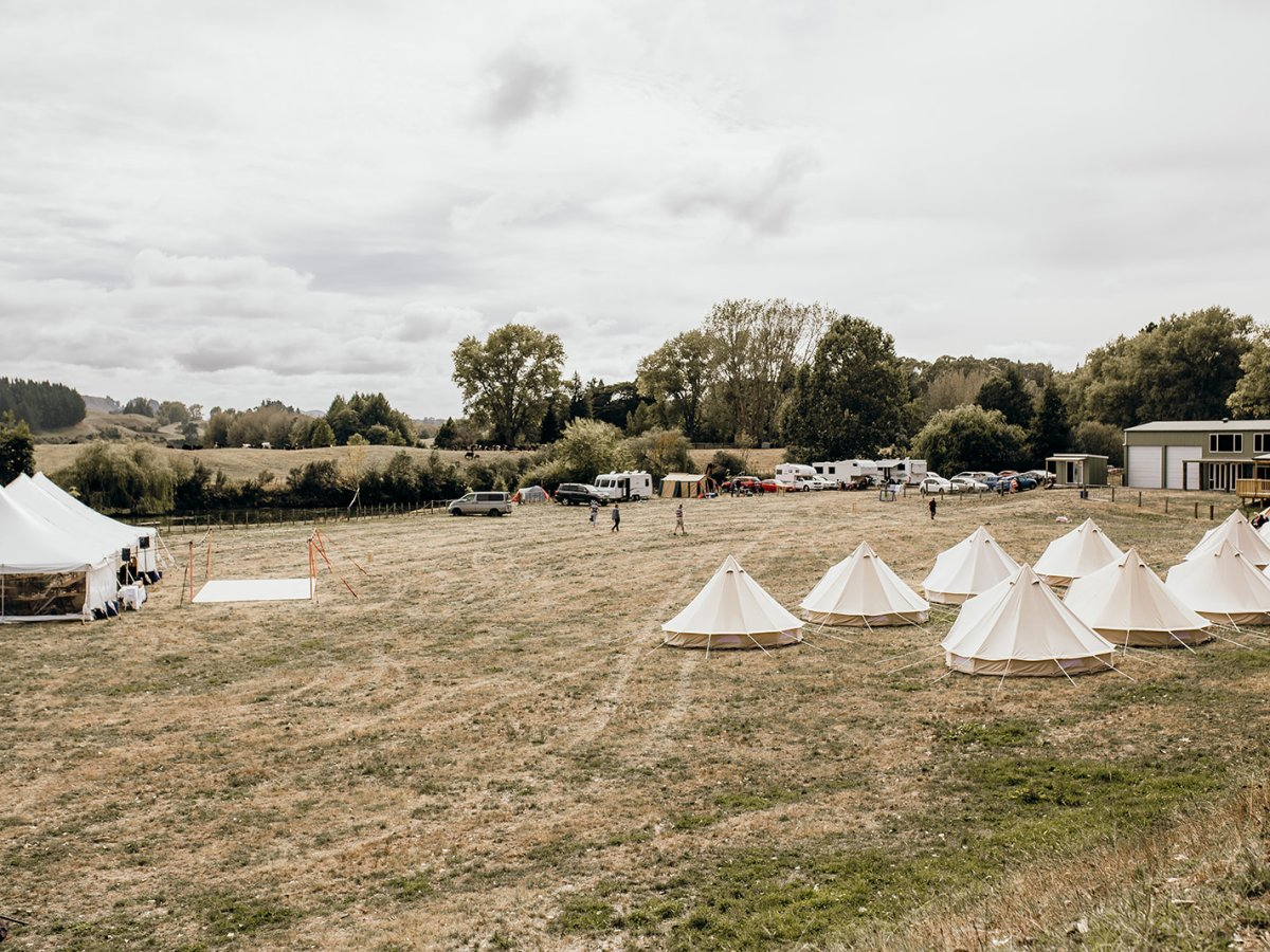 Several glamping tents and a marquee set up in a paddock ready for a wedding.