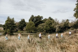 A line of bridesmaids and groomsmen pick their way through the long grass of a paddock.