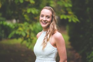 Jodie Munro in a white dress with a background of greenery