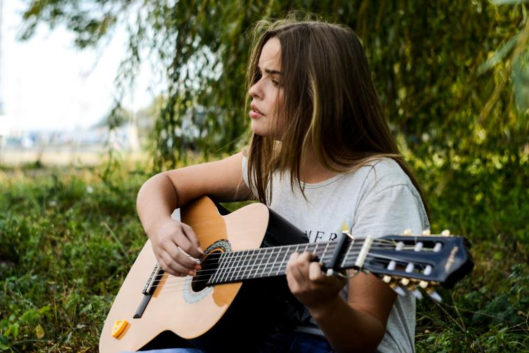 A lady sits outside beneath a tree, a look of love and passion on her face as she strums her guitar