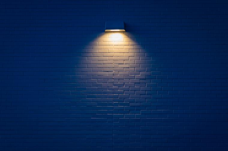 one single downlight highlights a small section of a white brick wall