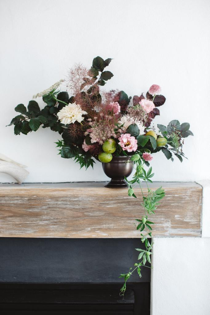 A dusty pink themed floral arrangement drapes over a wooden hearth adding drama and elegance