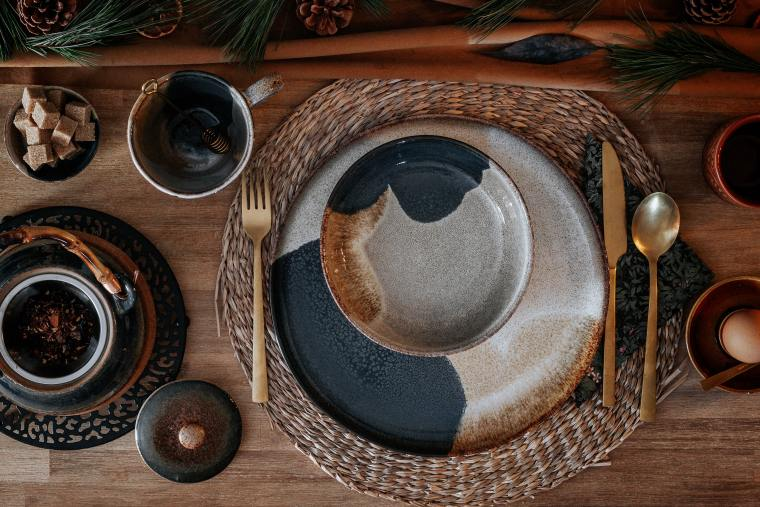 A moody table setting of dark patterned plates and bowls sitting atop a circular cane placemat and a wooden table.
