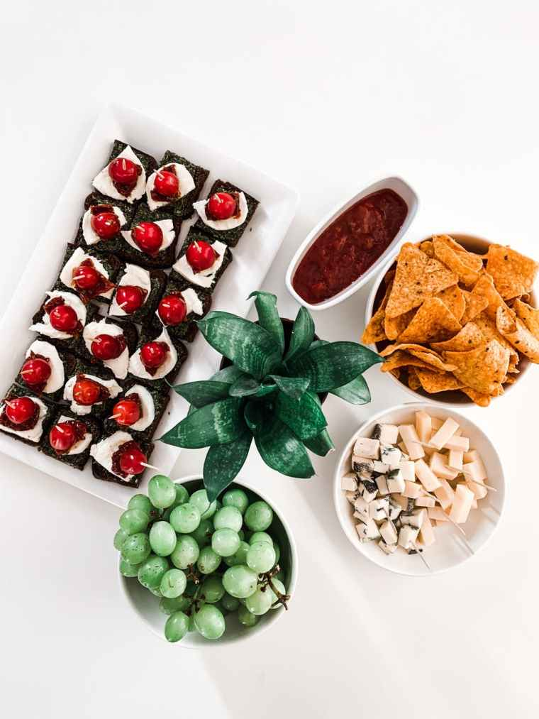 Looking down on a table a dark green plant is surrounded by delicious and colourful looking wedding canapes