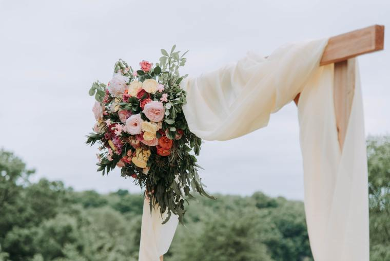 A light wood wedding arch draped with soft white fabric and a colourful bouquet in the upper left corner