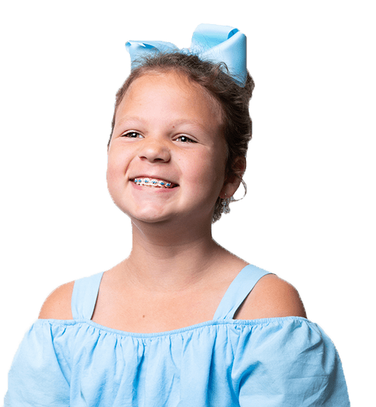 Young girl smiling with blue bow in hair, blue metal braces, off-the-shoulder blue shirt