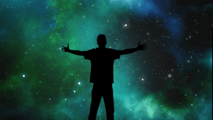 image of the universe with blue, green, and stars with a silhouette of a person standing in front with arms outspread.