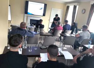 Attendees at their desk at the training session in Cork, watching the trainer giving the presentation.