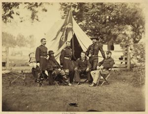 Maj. Gen. Phillip Sheridan, standing in he center underneath the guidon, surrounded by his subordinates. To Sheridan's left is Wesley Merritt and Alfred Torbert, whose men the Confederates around Old Cold Harbor on May 31.