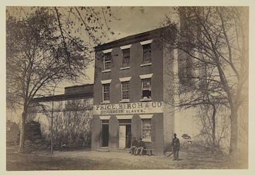 Photograph showing a Union army guard and other men in front of a building designated Price, Birch & Co., dealers in slaves, at 1315 Duke St., Alexandria, VA. Before that, the premises were owned by the slave-trading firm Franklin & Arm-field. The Union army used the former slave jail to house Confederate prisoners. (courtesy LOC)