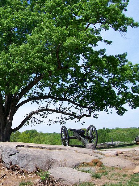 """Gettysburg Battlefield, Adams County PA: This photograph was taken from the backside of """"Devil's Den"""" at Gettysburg Battlefield in Pennsylvania. This is my favorite shot that I've taken to date as the contrast between the beautiful trees and the grimly positioned Federal cannon symbolize the contradiction of war."""