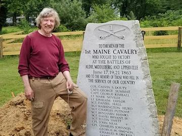 Steve Bunker stands beside 1st ME Cav monument