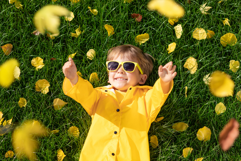 young girl wearing yellow jacket and sunglasses laying on grass as leaves fall around her