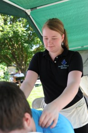 Jennifer de-stresses a patron at the Jennifer Michelle Massage booth.