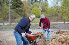 Tim and Bryce fill a wheelbarrow with mulch.