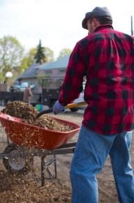 Bryce fills a wheelbarrow with mulch.