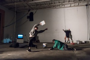 Three man dancing in a space full of object (buckets, tv, bags, microphone, etc.)