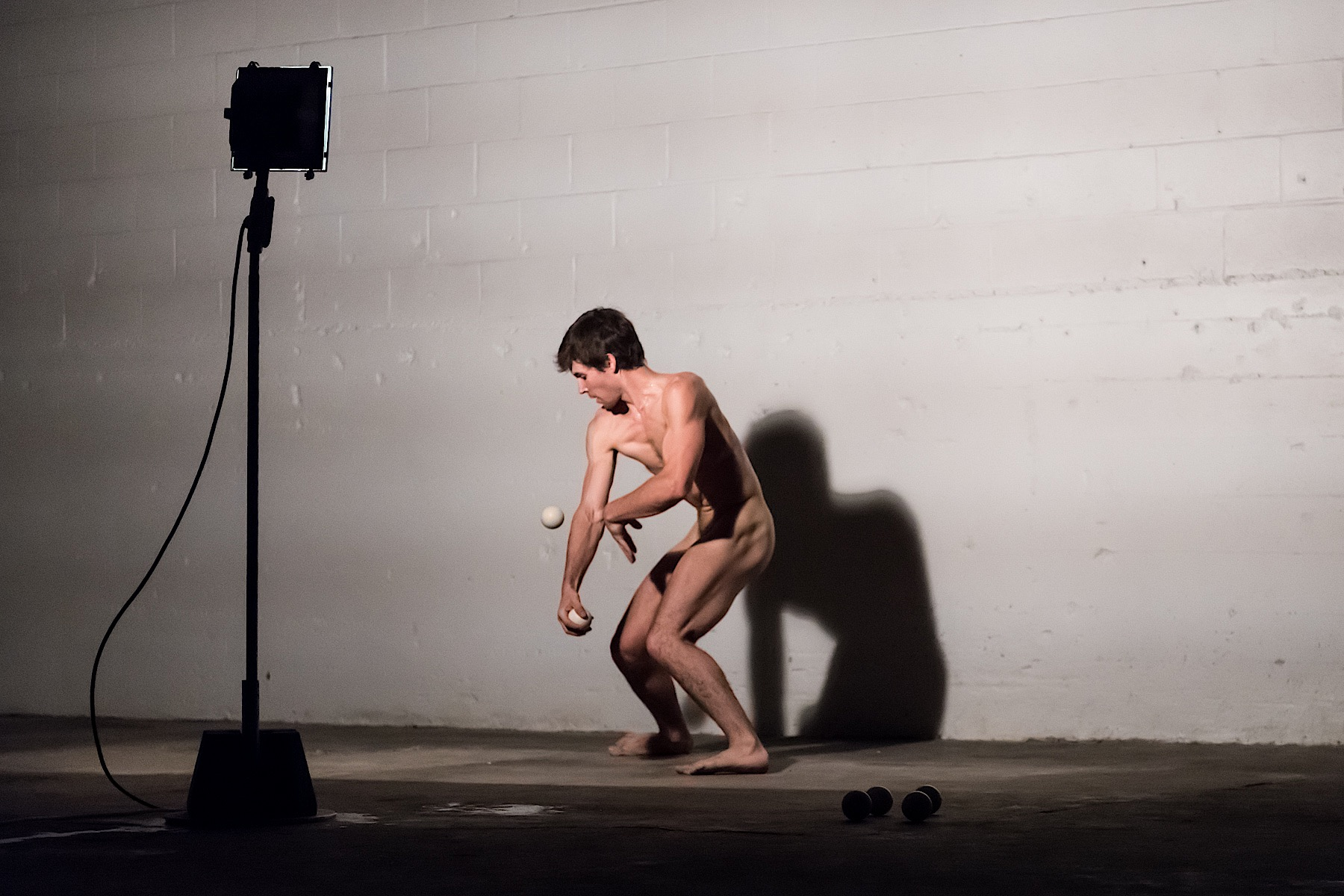 Naked person juggling with two balls