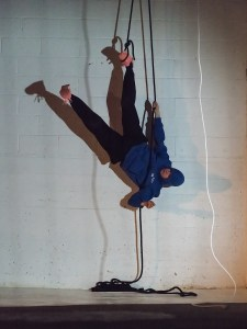 Person hanging upside down from a rope attached to her foot