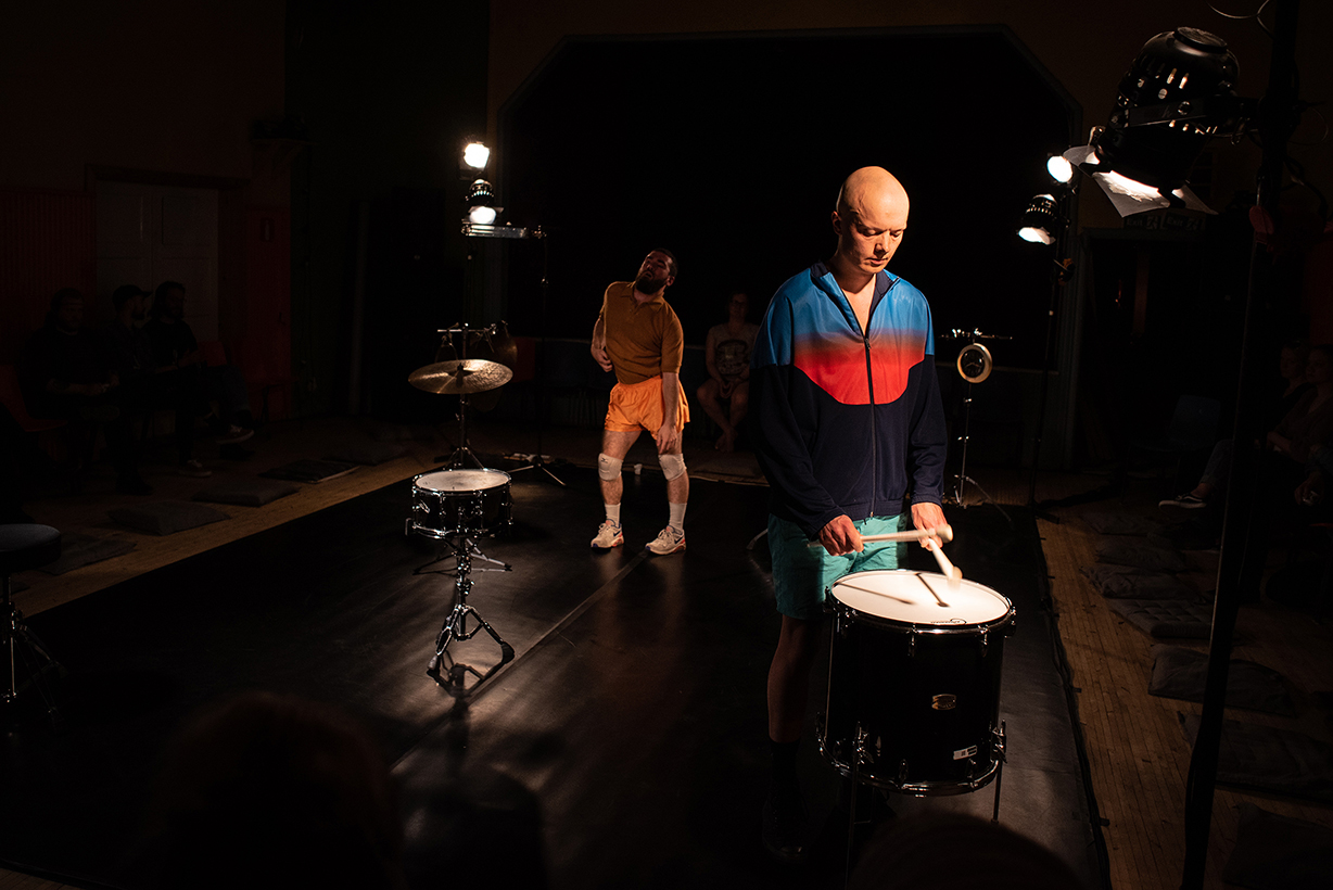 Emile dancing and Olavi drumming in a square space full of drums