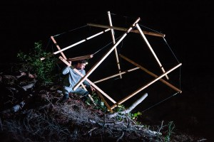 Person manipulating a big tansegrity structure made of wood and ropes, at night