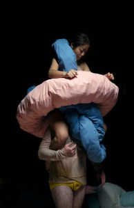 Dancer siting on the shoulders of an other dancer, holding 2 donut shaped cushions