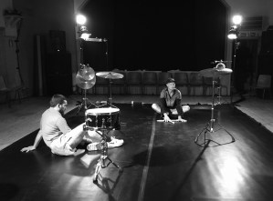 a square space full of drums and cymbals where Emile and Olavi are sitting