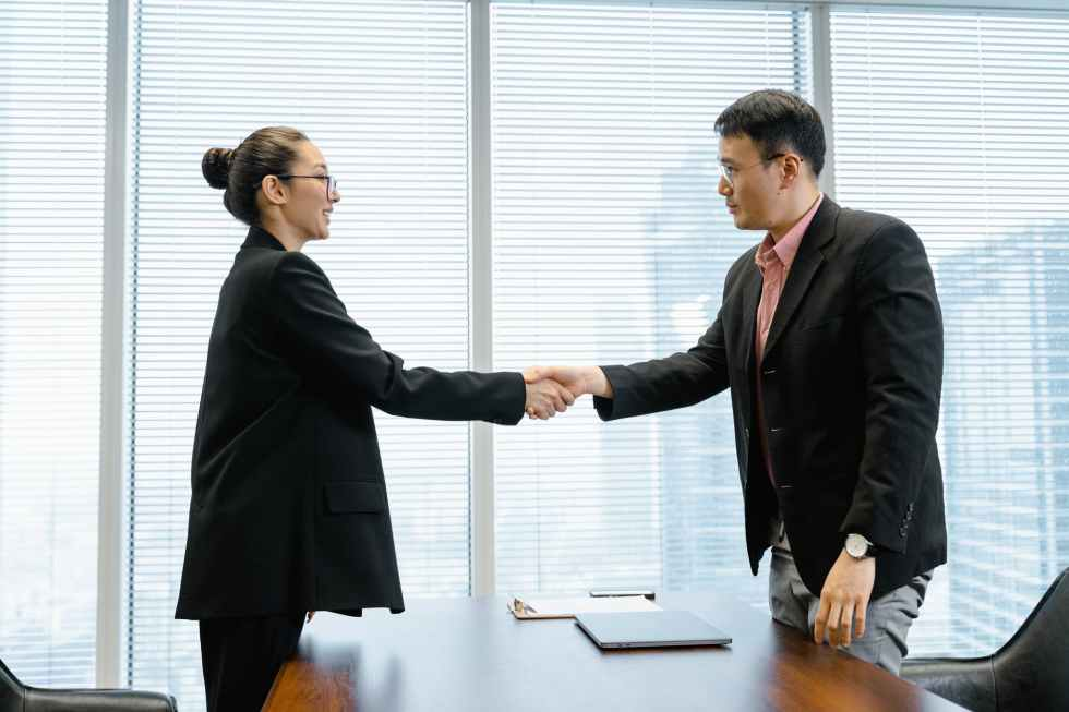 a man and a woman shaking hands, after she hires a Business Consultant