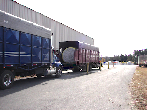 Trucks arriving at the gin with bales of cotton