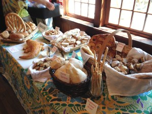 a table with many baskets of bread, all labeled