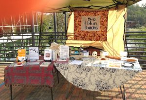 tables set up under tent with books for sale, dishes and containers with bread ad dough, labeled with signs