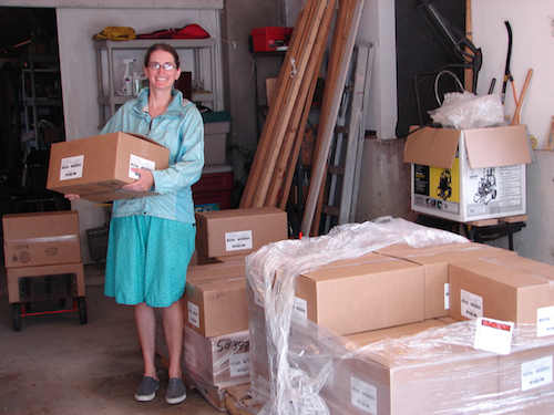 Emily in her parents' garage with books on a pallet