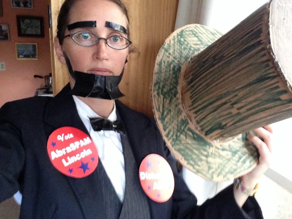 "Emily dressed as Abraham Lincoln with a vest and suit, with a duct tape beard and bowtie, holding a top hat and wearing buttons that say ""AbraSPAM Lincoln"" and ""Dishonest Abe"""