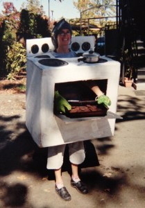 Emily inside a box painted like an oven, with a small pot glued on top and a pot lid on her head; she is holding a tray of cookies out the door with potholders on her hands