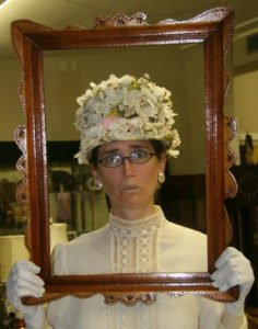 Emily wearing a flowered 1900 hat and fancy shirt, holding a picture frame