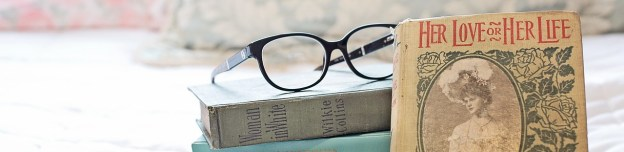 a stack of old, romantic-looking books with glasses on top