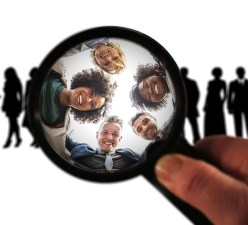 silhouettes of people with a magnifying glass showing the faces of five people, all smiling