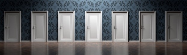 a row of identical doors in a wall with fancy wallpaper, and a polished wooden floor