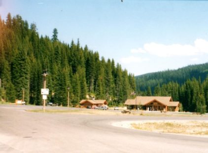 two log structures with an American flag flying and a parking lot, alongside the road, with a backdrop of evergreen trees