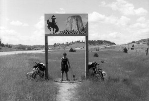 woman standing with two bikes at the border of Wyoming, with a sign overhead