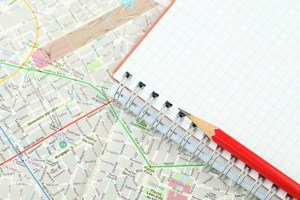 a pencil and blank notebook on top of a map of a city