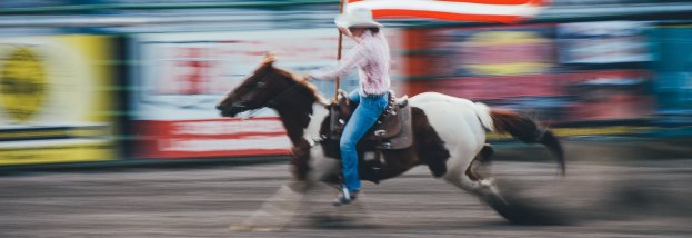 cowboy riding horse holding American flag, with blurry stadium seats in back