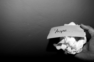 word hope on a piece of paper, atop a crumpled piece of paper in a hand
