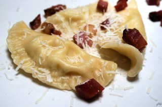 pierogies with shredded cheese and bits of dates on top