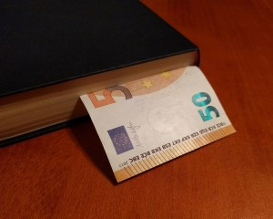 a book with a money bill sticking out of it