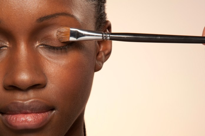 Woman with eye make up brush on eye